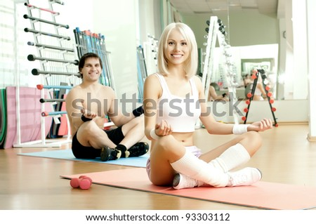 happy cutie athletic girl and guy,  execute exercise in pose lotus and smile, in  sport-hall - stock photo