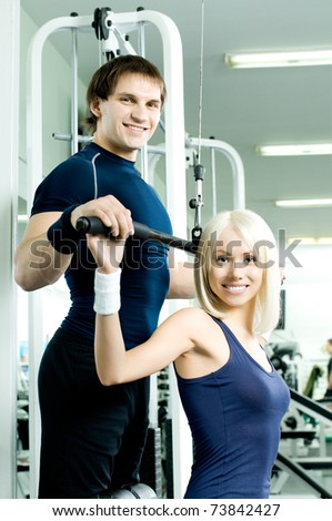 happy cutie athletic girl and guy,  execute exercise on sport-apparatus, in  sport-hall, look on camera and smile