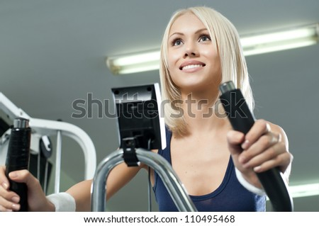 happy cutie athletic girl ,  execute exercise on exercise bicycle  and smile, in  sport-hall