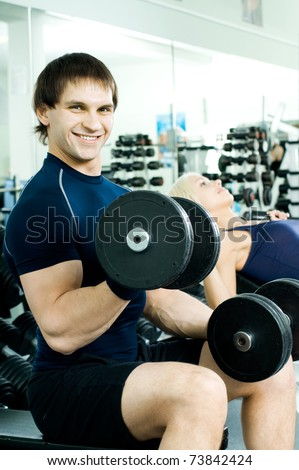 happy cutie athletic guy,  exercise with dumbbells, in  sport-hall, look on camera and smile