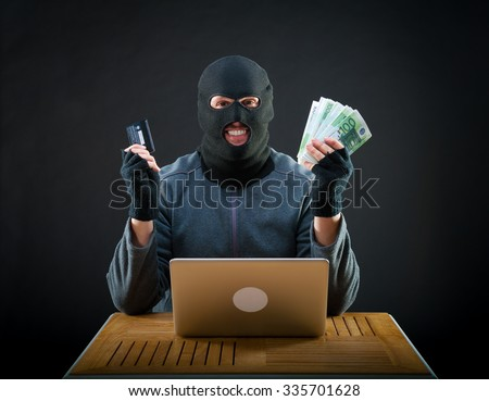 Happy cybercriminal man holding euro cash and stolen credit card - stock photo