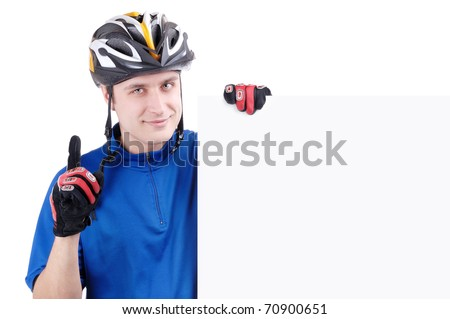 Happy cyclist in gloves, helmet and blue jersey holding a blank sign in front of him