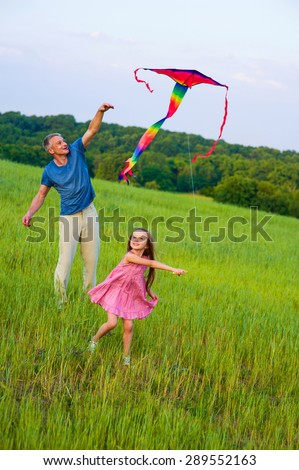 Happy dad and daughter flying a kite together.