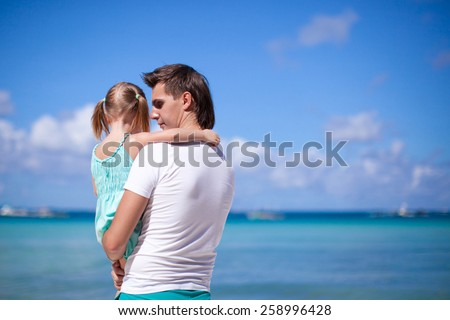 Happy dad and his adorable little daughter at tropical beach - stock photo