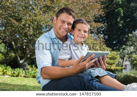 Happy dad and son smiling in a park with a tablet pc - stock photo