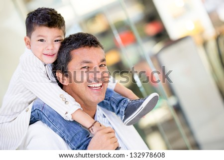 Happy dad carrying his son in his shoulders at the mall - stock photo