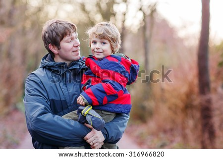 Happy dad holding his son, little funny kid boy on arm, on cold day, walking together in a park in spring, autumn or winter. Happy, joyful family.
