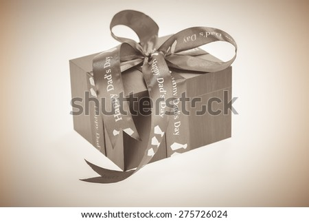 Happy Dad's Day message on a ribbon wrapped around a gift box in sepia tone and vignette effect  - stock photo
