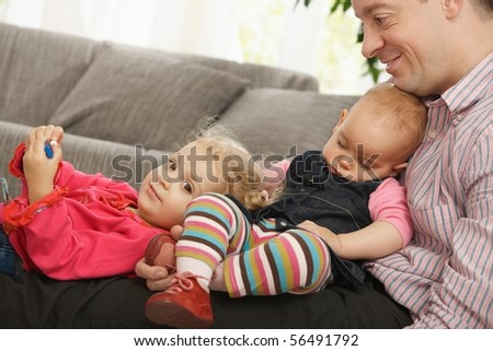 Happy dad sitting with smiling toddler and sleeping baby in lap at home.