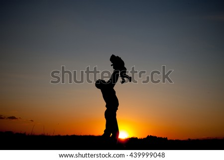 Happy dad throws the baby at sunset - stock photo