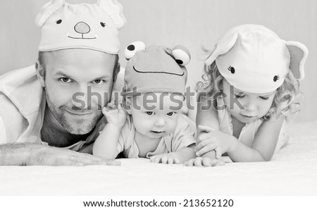 happy dad with kids in funny hats lying on the bed ( black and white ) - stock photo
