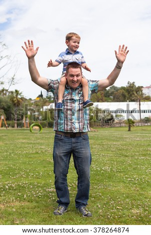 Happy daddy and his son having fun in the park outdoors. Happiness, fatherhood and childhood concept. - stock photo