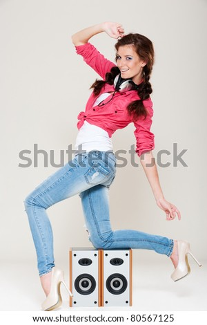 happy dancing girl with headphones on her neck posing near speakers - stock photo