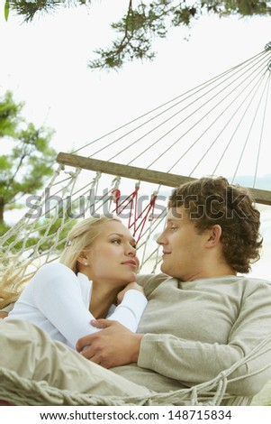 Happy dates looking at each other and smiling while lying in hammock - stock photo