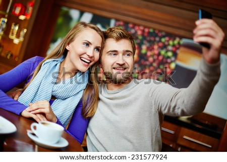 Happy dates taking their selfie on cellular phone