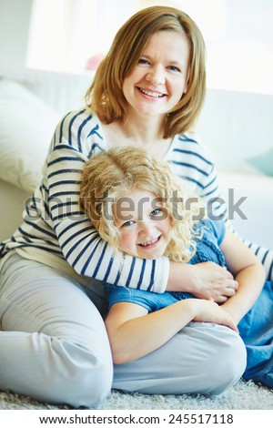Happy daughter and mother staying at home on weekend - stock photo