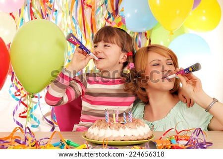 happy daughter and mother with trumpets and balloons on birthday party