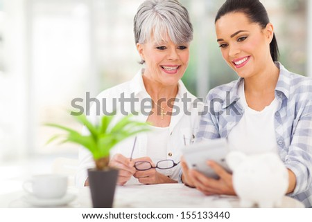 happy daughter helping middle aged mother calculate her retirement investments - stock photo