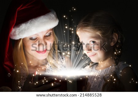 Happy daughter receiving Christmas gift from mother - stock photo