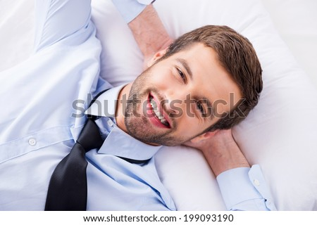 Happy day dreamer. Top view of handsome young man in shirt and tie holding hands behind head and smiling while lying in bed  - stock photo