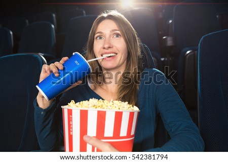 Happy day. Shot of a cheerful mature woman enjoying a comedy movie at the cinema sipping her drink holding popcorn bucket food eating drinking snack industry entertainment tasty happiness concept