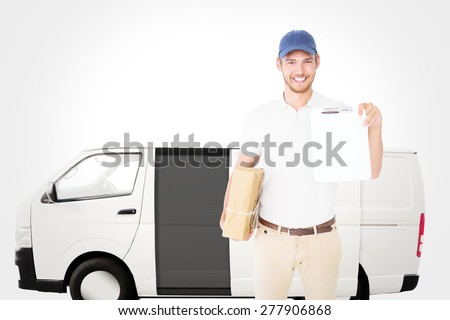 Happy delivery man holding cardboard box and clipboard against white delivery van - stock photo