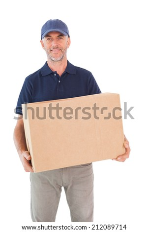 Happy delivery man holding cardboard box on white background - stock photo