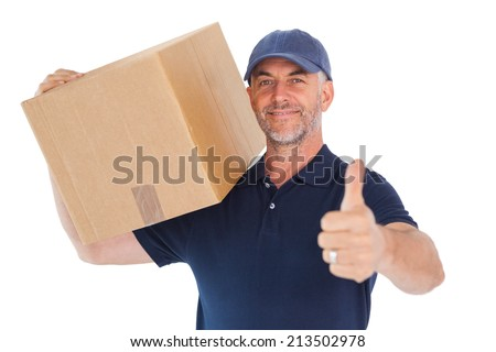 Happy delivery man holding cardboard box showing thumbs up on white background - stock photo
