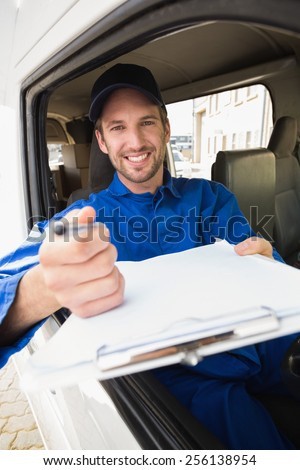 Happy delivery man showing clipboard to sign to customer outside the warehouse - stock photo