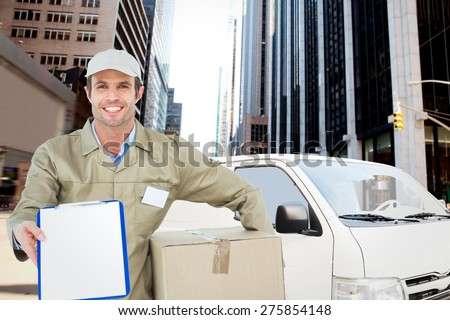 Happy delivery man with box showing clipboard against new york street - stock photo