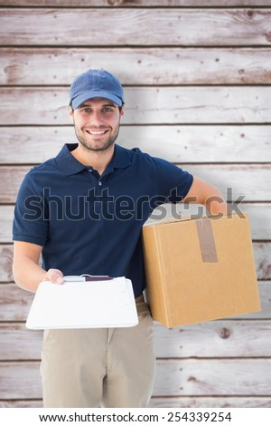 Happy delivery man with cardboard box and clipboard against wooden planks - stock photo