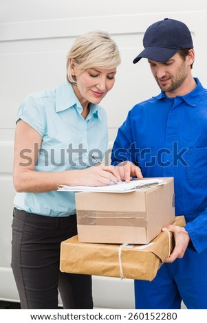 Happy delivery man with customer outside the warehouse - stock photo