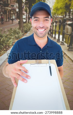 Happy delivery man with package and clipboard against bike path in amsterdam - stock photo