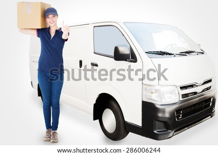 Happy delivery woman holding cardboard box against white delivery van - stock photo