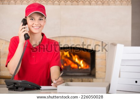 Happy delivery woman of pizza in red uniform with pen and diary for placing order and boxes of pizza. - stock photo