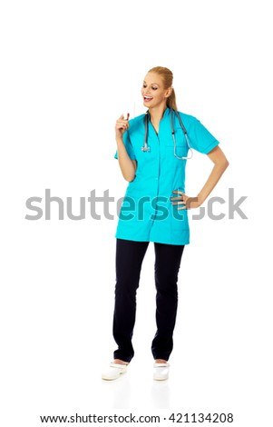 Happy dentist woman with stethoscope holding tooth model - stock photo