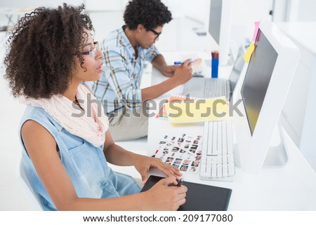 Happy design team working at desk in their office - stock photo