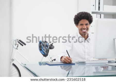 Happy designer drawing on graphics tablet in his office