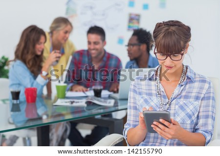 Happy designer using a tablet pc with colleagues discussing behind - stock photo