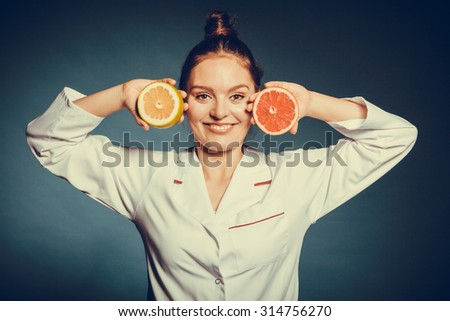 Happy dietitian nutritionist holding grapefruit having fun. Woman promoting healthy food fruit. Right eating nutrition and slimming concept. - stock photo