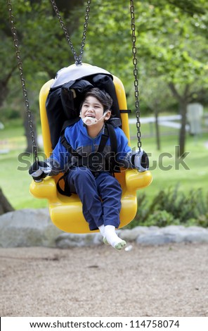 Happy disabled boy on yellow handicap swing - stock photo
