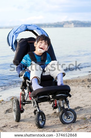 Happy disabled five year old boy in wheelchair on the beach - stock photo