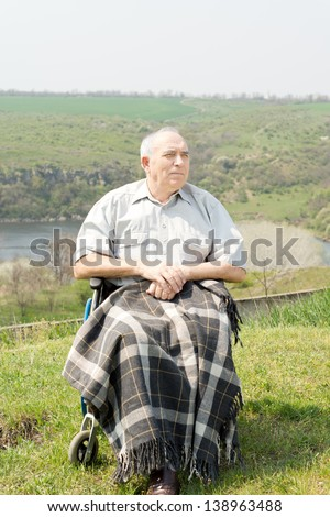 Happy disabled senior man enjoying the sun sitting on a hilltop with scenic views with a blanket over his legs