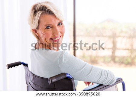 happy disabled woman in wheelchair looking back - stock photo