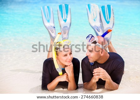 Happy diver couple lying down on the beach, wearing mask and flippers for snorkeling, enjoying extreme water sport, active summer time vacation - stock photo