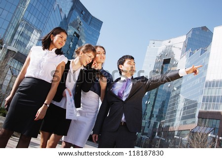 Happy diverse group of executives pointing over business center. Outdoor - stock photo