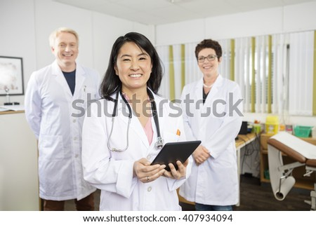 Happy Doctor Holding Tablet Computer While Standing With Colleag - stock photo