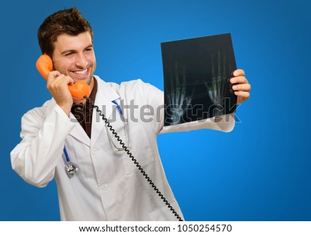 Happy Doctor Holding X-ray And Telephone On Blue Background