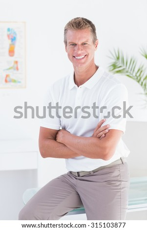 Happy doctor looking at camera with arms crossed in medical office