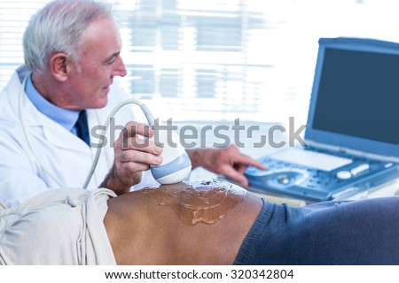 Happy doctor pointing towards screen in hospital - stock photo